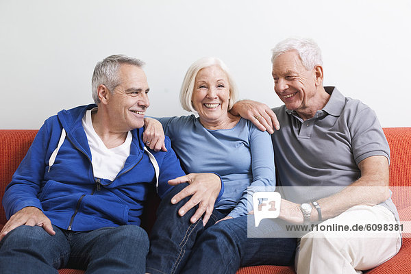 Senior men and woman sitting on couch  smiling