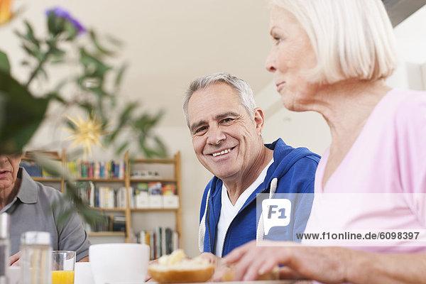 Senior men and women having breakfast