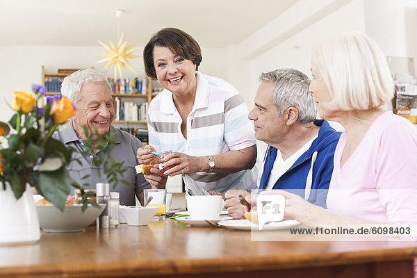 Senior men and women eating food  smiling