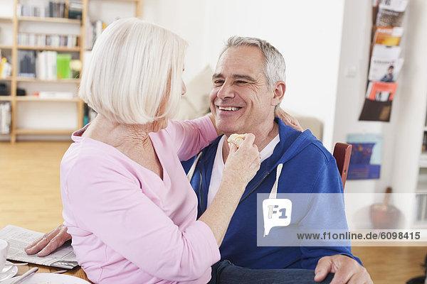 Seniorin sitzt auf dem Schoß des Mannes  lächelnd