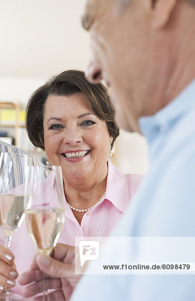 Senior man and woman drinking sparkling wine  smiling
