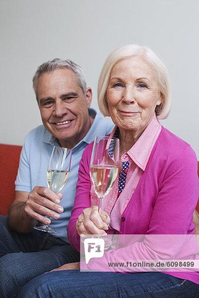 Senior Mann und Frau trinken Sekt  lächelnd