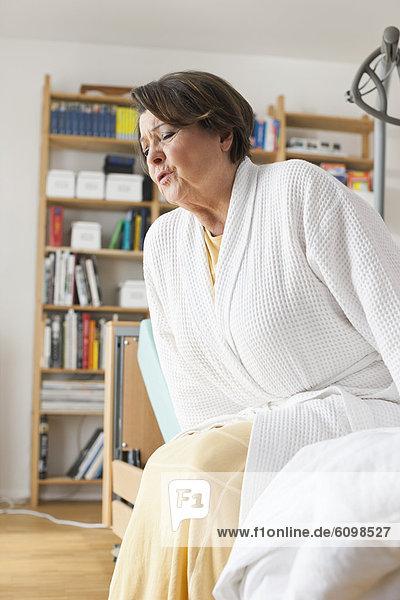 Seniorin beim Aufstehen aus dem Krankenbett