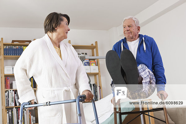 Senior woman standing and man playing with walking frame