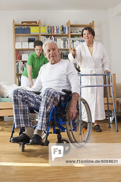Senior man sitting on wheelchair  woman with walking frame