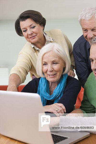 Senioren Männer und Frauen beobachten Bilder auf dem Laptop