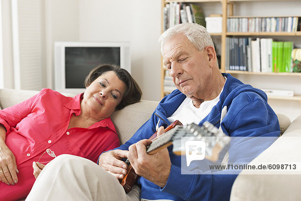 Senior Mann spielt E-Gitarre auf dem Sofa  Frau sitzt daneben