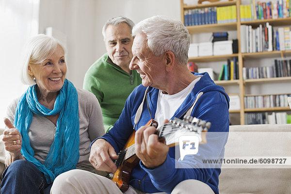 Senior Mann spielt E-Gitarre  Mann und Frau sitzen daneben