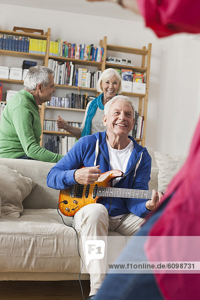 Senior man playing electric guitar  man and woman in background