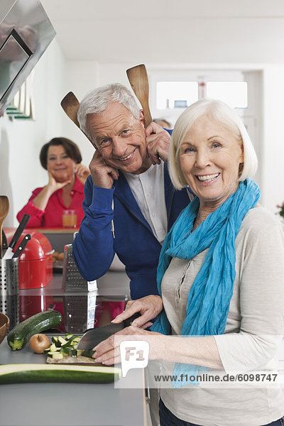 Man and women cooking food  smiling
