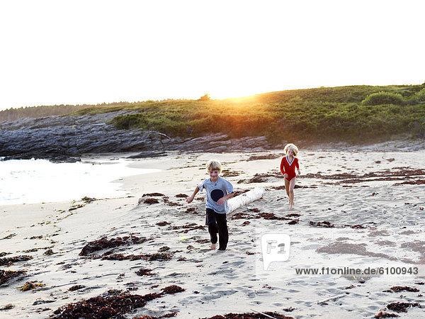 siblings chase on beach