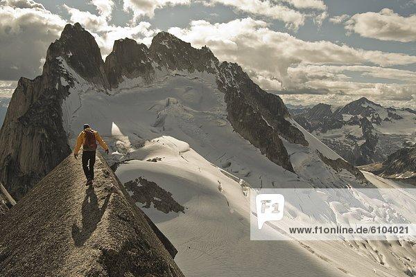 Man balancing along a granite edge  Bugaboo Provincial Park  Radium  British Columbia  Canada.