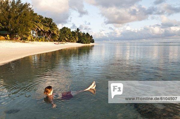 Woman relaxing in a lagoon at sunset  Rarotonga  Cook Islands.