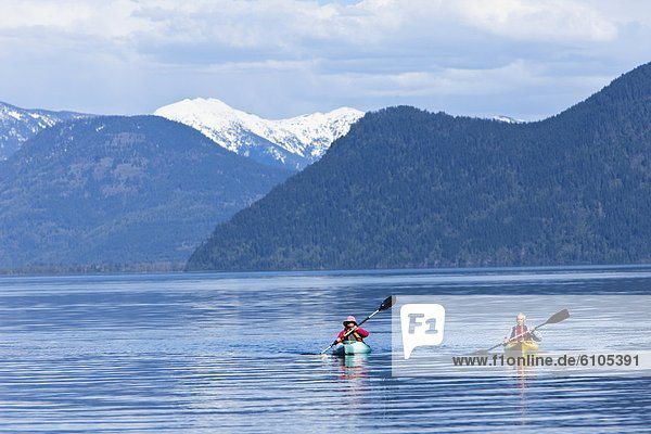 An happy adventurous retired couple kayaking on a huge calm lake in Idaho.
