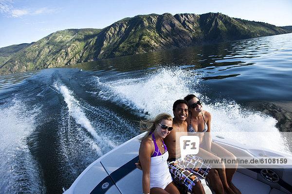 Wakeboarding  Wake boarding  sitzend  lächeln  See  Boot  jung  3  lachen  Idaho