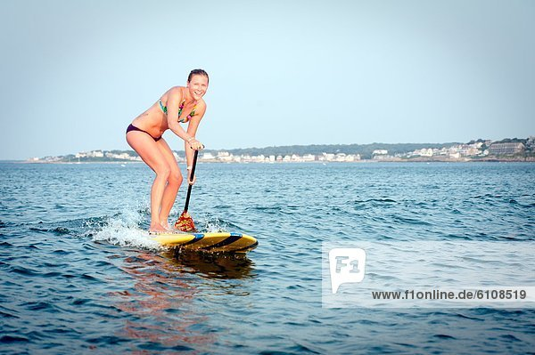 A young woman enjoys her stand up paddle board in the ocean.