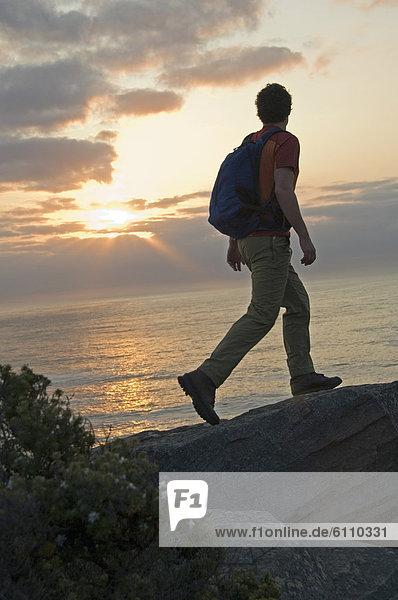 Hiker on cliff trail on rocky ocean coast.