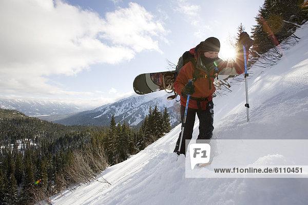 Snowboardfahrer  bergauf  Klettern  unbewohnte  entlegene Gegend
