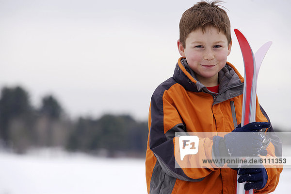 Portrait of young boy with xc skis.