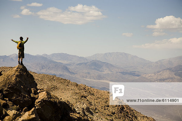 A man stands with arms extended at the summit of a peak in Death Valley National Park  California.