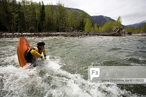 A playboater enjoys a small wave on a river.