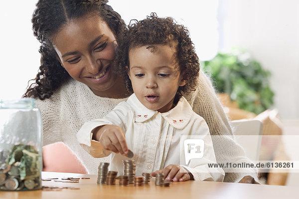 Mutter und Tochter zählen Münzen