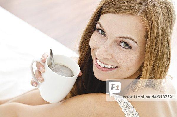 Lächelnde junge Frau mit einer Tasse im Bett