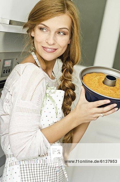Lächelnde junge Frau mit einem Kuchen in der Küche Lächelnde junge Frau mit einem Kuchen in der Küche