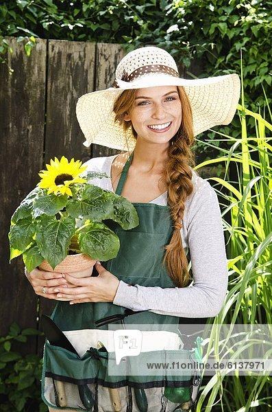Lächelnde junge Frau mit einer Sonnenblume im Garten