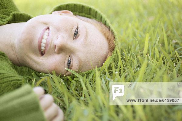 Portrait einer jungen Frau auf Gras liegend