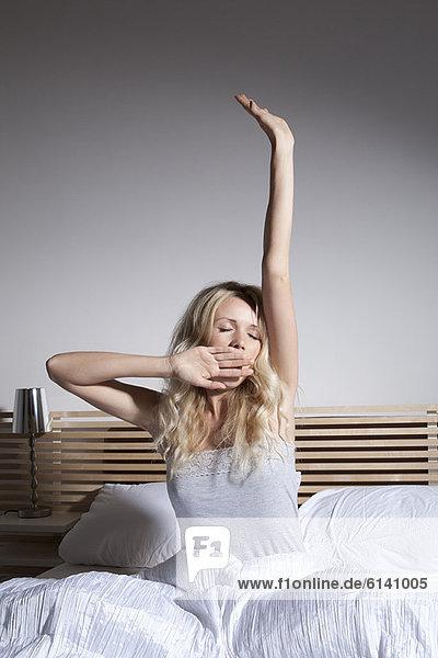 Gähnende Frau streckt sich im Bett