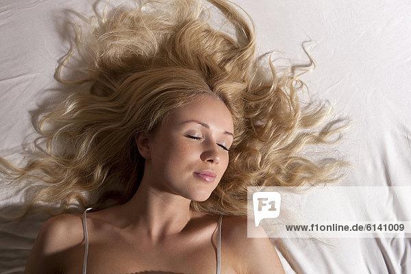 Lächelnde Frau schläft im Bett
