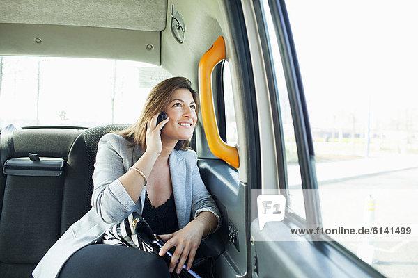 Geschäftsfrau am Handy im Taxi
