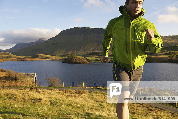 Wanderer  der den grasbewachsenen Hang hinaufläuft
