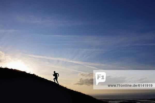 Silhouette eines Wanderers  der den Hang hinaufläuft