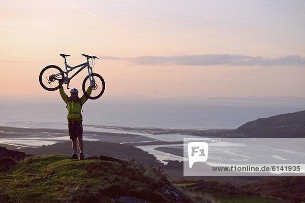 Mann mit Fahrrad auf dem Hügel