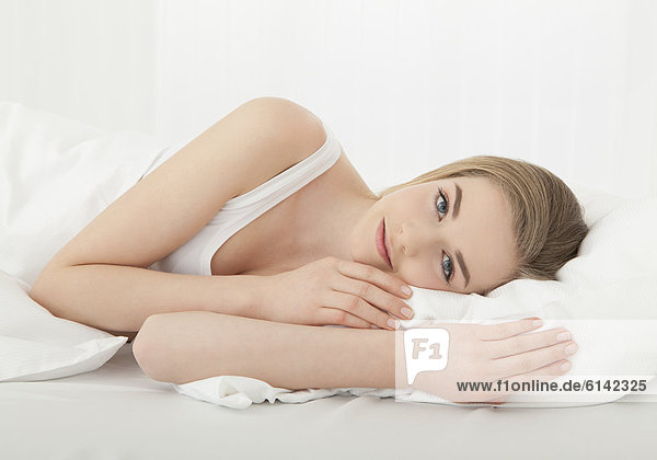 Junge Frau liegt in Bett