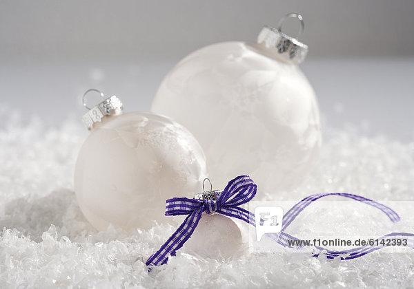 Weihnachtsarrangement  weiße Kugeln in Kunstschnee