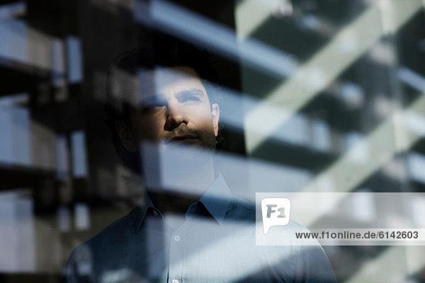Geschäftsmann mit Blick durchs Fenster