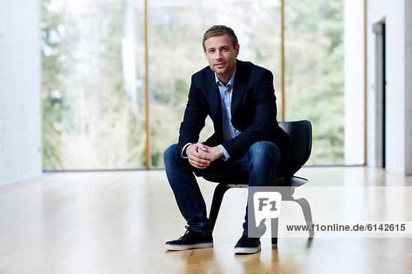 Geschäftsmann auf schwarzem Stuhl sitzend  Portrait