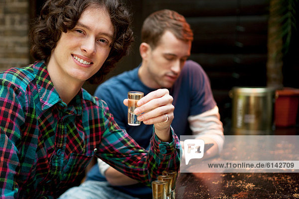 Two men at bar  one holding shot glass
