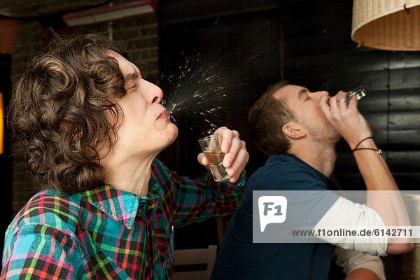Zwei Männer  die Schüsse trinken.