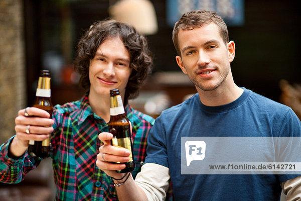 Männliche Freunde posieren mit Bierflaschen
