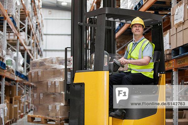 Mann beim Transport von Beständen im Distributionslager