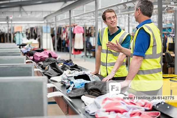 Zwei Männer beim Sortieren von Kleidung auf dem Förderband im Lager