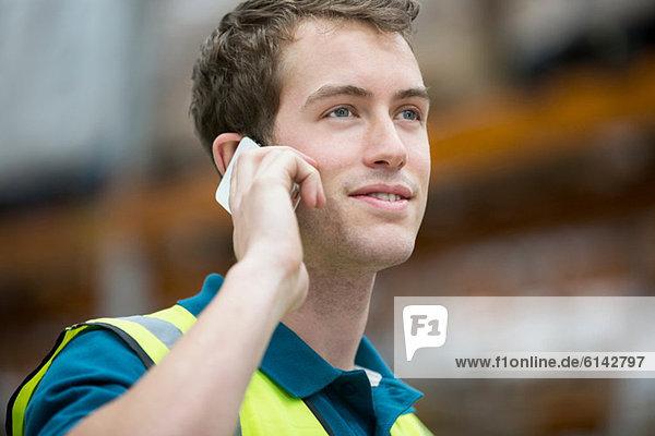 Mann auf dem Handy im Lagerhaus  Portrait