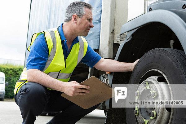 Mann überprüft LKW-Reifen