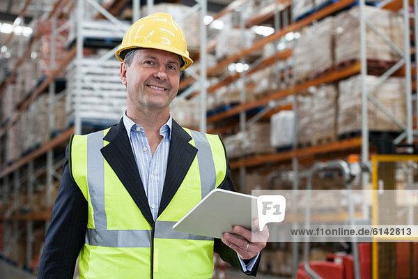 Mann mit digitalem Tablett im Lager  Portrait