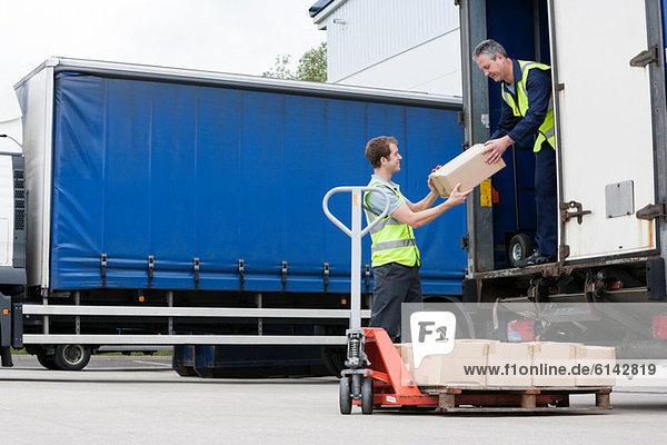Zwei Männer beim Entladen von Kartons vom LKW