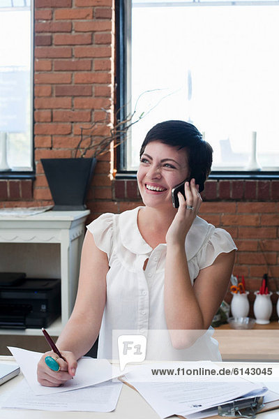 Businesswoman in office on phone  portrait